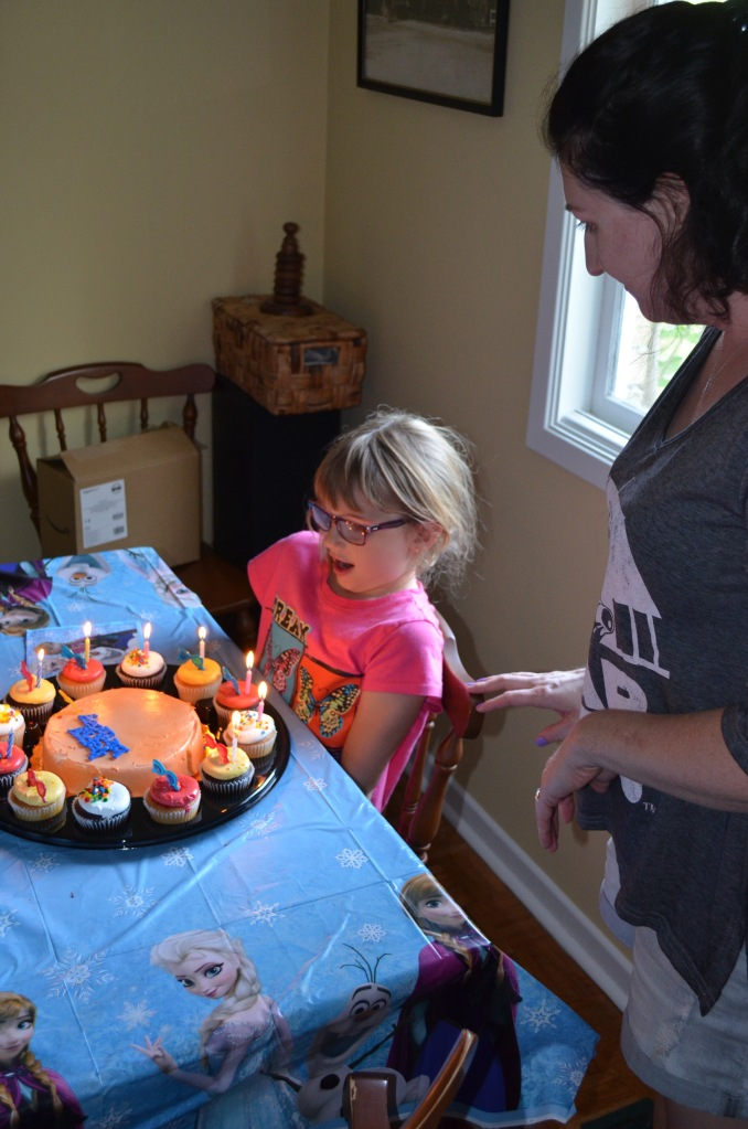 Abby blowing out the candles on her cupcakes