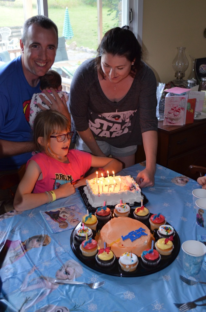 Abby blowing out her 2nd cake with Mom, Dad and cousin Eva looking on.