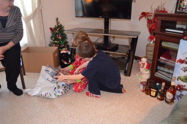 Aiden looking at one of Abby's gifts.