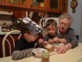 Macklan & Aiden helping Mama decorate her gingerbread house