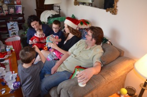 Melissa holding Eva, Aiden, Julie, Peter and Macklan opening presents.