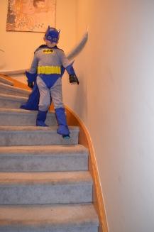 Aiden strutting down the stairs as Batman