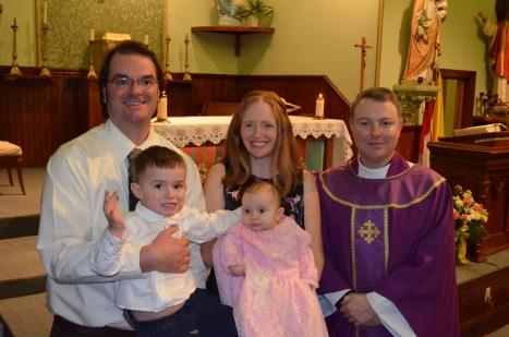 Peter holding Macklan, Julie holding Eva, with Father Cruikshank.