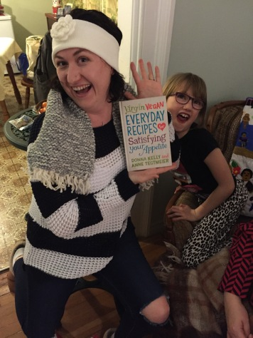 Melissa posing with her new scarf and Vegan cookbook with Abby in the background.