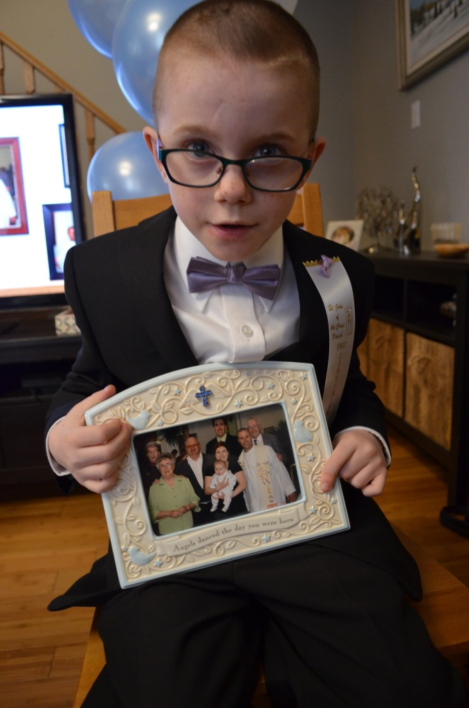 Aiden holding a picture from his baptism.