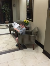 Aiden reading the paper in the lobby of the Holiday Inn