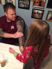 Uncle Jason showing Abby his tattoos