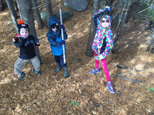 Ninja pose: Macklan, Aiden & Abby walking in the field behind Mama & Papa's