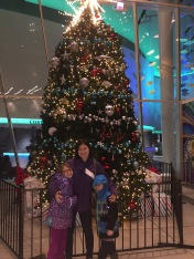 Melissa and the kids in front of the Christmas tree at Ripleys