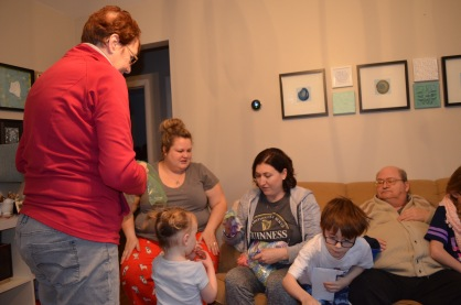 Grandma, Megan, Violet, Aiden, Bruce watching Melissa open a gift.