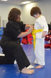 Aiden receiving his Yellow Belt from Mrs. Sanderson