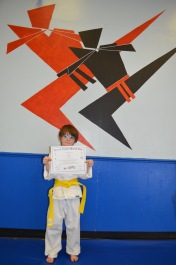 Aiden displaying his Yellow Belt Certificate