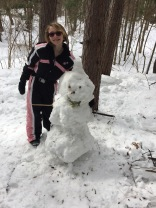 Abby with the snowman that she made with her Dad along the snowshoe trail