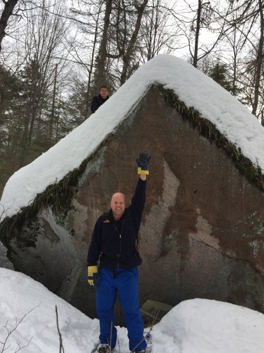 Aaron with Steven (background) in front of huge stone along snowshoe trail