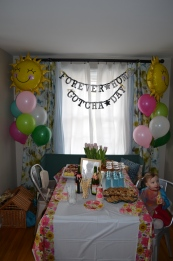 Violet at her party table. Banner Reads: `Forever Home. Gotcha Day`