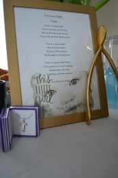 "The poem, golden wishbone and necklace that was on the table during the party. The poem is titled: ""A Chosen Child: Violet"""
