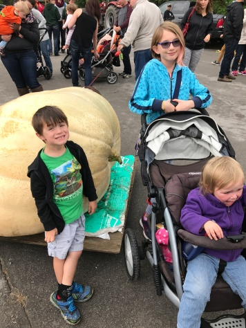 Macklan, Abby, & Eva in front of the one of the big pumpkins