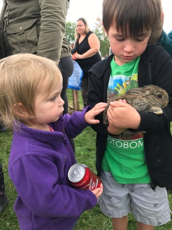 Macklan & Eva petting a rabbit from the petting zoo
