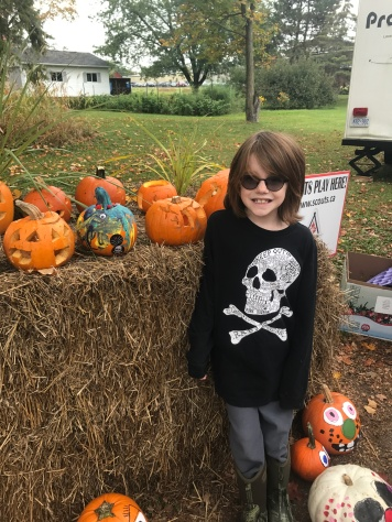 Aiden in front of the pumpkin he made at school
