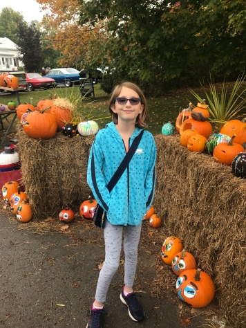 Abby in front of the pumpkin she made at school