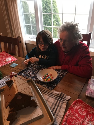 Mama helping Aiden build the gingerbread house