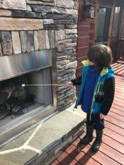 Aiden roasting marshmallows on the deck